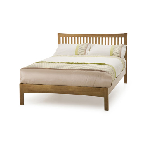 wooden bed frame with dressed mattress on