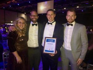 3 men and 1 lady from sussex beds at national business awards ceremony with award in frame