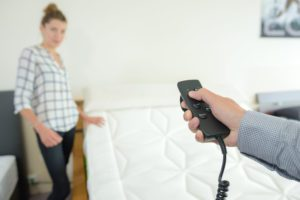 woman stood beside adjustable bed with man holding black controller time to adjust