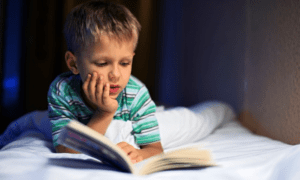 young boy lying on a bed reading a book