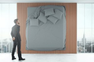 Smartly suited man looking at dressed bed with scattered pillows attached to wall showing bed in modern culture