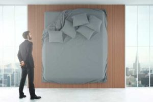 smartly dressed man looking at bed hanging on wall dressed with scatter cushions