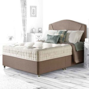 bloomsbury 7200 divan bed with brown base and headboard in room setting, dressed with several cushions and a throw - Sussex Beds