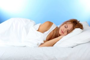 young woman laying in bed with white bedding and white pillow