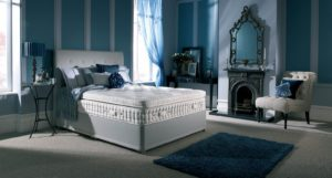 pillow top bed with headboard and scatter cushions in bedroom with fire place