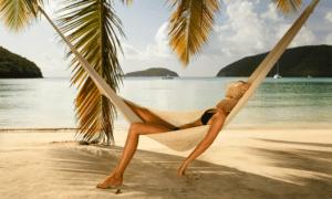 woman in bikini sleeping in a hammock under palm tree on beech