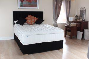 Luxury divan bed with headboard in bedroom setting
