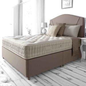 Marquis & Moore Islington 8800 divan bed in a room setting with wooden floor. Dressed with cushions and matching beige headboard and base - Sussex beds