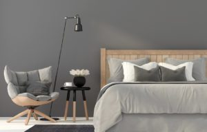 grey bedroom setting with bed and wooden stool, a chair and a floor standing lamp