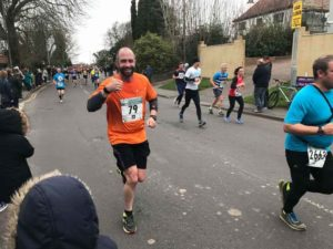 male in black shorts and orange vest running on a road