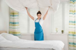 women lifting white duvet over her head above a white bed