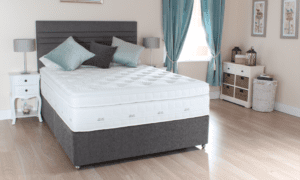 Divan bed with therma-gel mattress and scatter cushions and headboard in bedroom setting