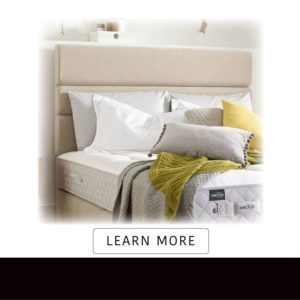 Nectus Hybrid upholstered padded beige headboard attached to divan bed covered with cushions and throws
