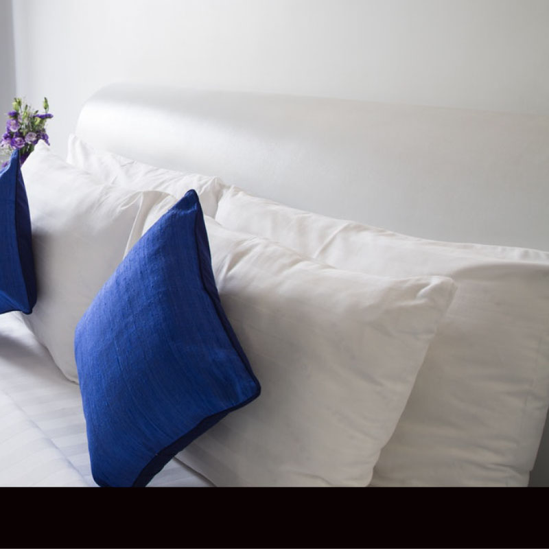 Bedding - white pillows on a bed with blue cushions - Sussex Beds