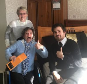 lady in wheelchair and man on bed with their thumbs up and happy