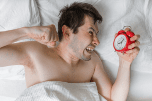 angry frustrated man laying in bed holding alarm clock with other fist clenched