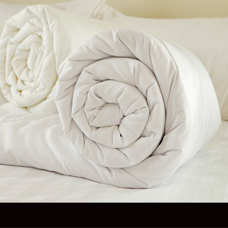 Bedding - White duvet rolled up on a bed - Sussex Beds