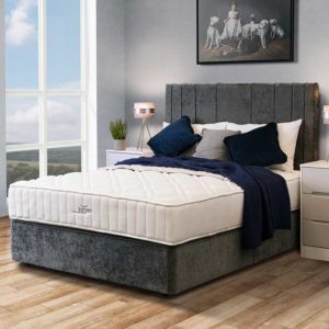 Nectus fusion revive divan bed with rectangular padded headboard in room setting next to large window. Bed dressed with cushions and pillows - Sussex Beds