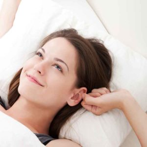 young women laying with her head on a white pillow smiling and touching her ear