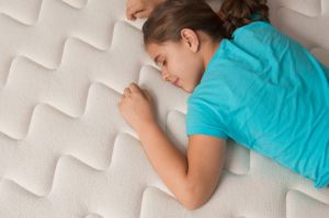 young women laying on her front on a mattress