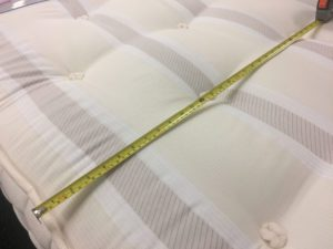 mattress with metal tape measure stretched across it
